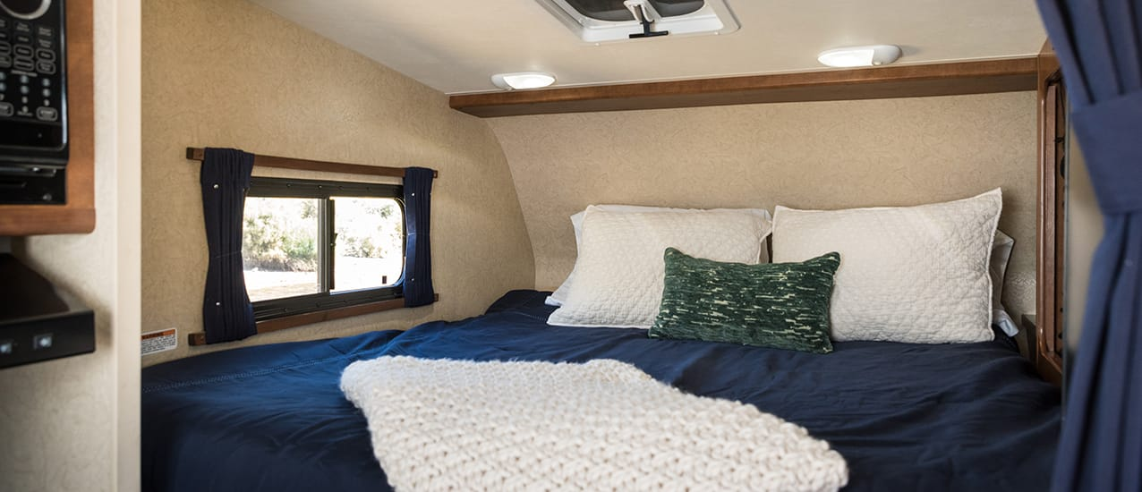 master bed in loft with quilt and pillows